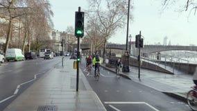 Οι ποδηλάτες οδηγούν σε μια πολυάσχολη πάροδο κύκλων στο Λονδίνο με τους φωτεινούς σηματοδότες κύκλων από τον ποταμό Τάμεσης και  απόθεμα βίντεο