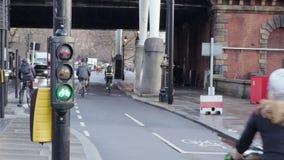Οι ποδηλάτες οδηγούν σε μια πολυάσχολη πάροδο κύκλων στο Λονδίνο με τους φωτεινούς σηματοδότες κύκλων από το εργοτάξιο οικοδομής απόθεμα βίντεο