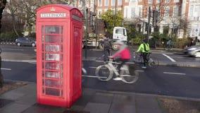 Οι ποδηλάτες σε μια πάροδο κύκλων πηγαίνουν μετά από ένα βρετανικό τηλεφωνικό κιβώτιο στη βροχή απόθεμα βίντεο