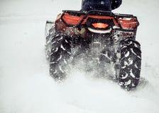 Ολισθήσεις ATV στο χιόνι Καθαρισμός των οδών του χιονιού με ένα τρακτέρ στοκ φωτογραφία