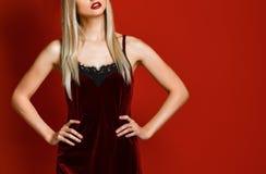 Ολόκληρος πυροβολισμός της πανέμορφης ζαλίζοντας γυναίκας στο προκλητικό φόρεμα βελούδου σφεντονών που στέκεται στο στούντιο και  στοκ φωτογραφίες
