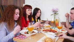 Ομάδα νέων φίλων που κάθονται στον καφέ με τον πίνακα, την κατανάλωση και την ομιλία απόθεμα βίντεο