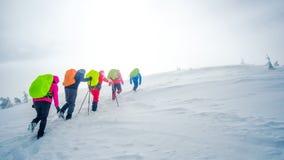 Ομάδα ορειβατών που πηγαίνουν στην κορυφή του βουνού το χειμώνα στοκ εικόνες