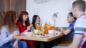 Ομάδα φίλων που κάθονται σε έναν καφέ και που έχουν μια συνομιλία φιλμ μικρού μήκους