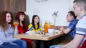Ομάδα φίλων που κάθονται σε έναν καφέ και μια ομιλία Μια νέα γυναίκα παίρνει ένα γυαλί με το ποτό σε το απόθεμα βίντεο