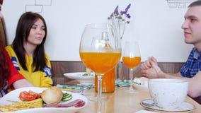 Ομάδα φίλων που κάθονται σε έναν καφέ και μια ομιλία Ποτήρι του χυμού από πορτοκάλι σε ένα πρώτο πλάνο φιλμ μικρού μήκους