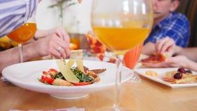 Ομάδα φίλων που κάθονται στον καφέ Επιτραπέζιο σύνολο των τροφίμων και των ποτών Λήψη των κομματιών pepperoni πιτσών απόθεμα βίντεο