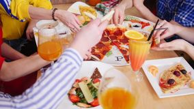 Ομάδα φίλων που κάθονται στον καφέ Επιτραπέζιο σύνολο των τροφίμων Λήψη των κομματιών pepperoni πιτσών απόθεμα βίντεο