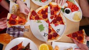 Ομάδα φίλων που κάθονται στον καφέ Λήψη των κομματιών pepperoni πιτσών φιλμ μικρού μήκους