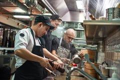 Ομαδική εργασία Αρχιμάγειρας εστιατορίων και δύο βοηθοί του στις ποδιές που μαγειρεύουν ένα νέο πιάτο σε μια σύγχρονη κουζίνα στοκ εικόνα