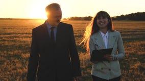 Ομαδική εργασία των επιχειρηματιών ο επιχειρηματίας και η επιχειρηματίας συζητούν το σχέδιο ομαδικής εργασίας στο πάρκο στο ηλιοβ απόθεμα βίντεο