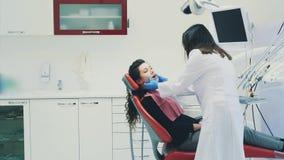 Οδοντίατρος και ασθενής Νέος όμορφος οδοντίατρος που επισκευάζει τα δόντια μιας όμορφης νέας γυναίκας στο γραφείο του οδοντιάτρου απόθεμα βίντεο