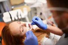 Οδοντίατρος που αρχίζει την κοινή λειτουργία του καθαρισμού του θηλυκού στόματος στοκ φωτογραφία με δικαίωμα ελεύθερης χρήσης