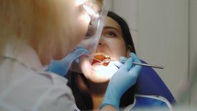 Οδοντίατρος που εξετάζει τα δόντια ενός ασθενή στο γραφείο οδοντιάτρων απόθεμα βίντεο