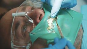 Οδοντίατρος που μεταχειρίζεται έναν υπομονετικό χρησιμοποιώντας εγκιβωτισμό 4K φιλμ μικρού μήκους