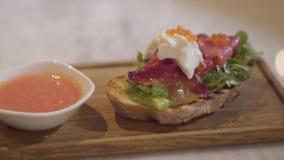 Ορεκτικός του εύγευστου ψωμιού με τα κόκκινα ψάρια, την κρέμα και το κόκκινο χαβιάρι σε μια ξύλινη κουζίνα επιβιβαστείτε στην κιν απόθεμα βίντεο