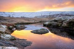 Ορμή του AR Pont, κοιλάδα ορμής, Ουαλία Χιονώδης σκηνή της ορμής Afon που ρέει προς craig goch κάτω από την πορτοκαλιά ανατολή με στοκ φωτογραφίες