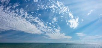 Ουρανός με τα μικρά σύννεφα πέρα από τη θάλασσα με έναν κυματοθραύστη και ένα αναγνωριστικό σήμα στοκ φωτογραφίες