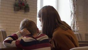 Οπισθοσκόπος μια γοητευτικοί νέοι μητέρα και ένας γιος κάθονται σε έναν πίνακα απόθεμα βίντεο