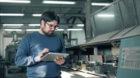 Ο άνδρας εργαζόμενος παρατηρεί μια λειτουργούσα μηχανή εκτύπωσης απόθεμα βίντεο