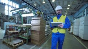 Ο άνδρας εργαζόμενος περπατά σε μια δυνατότητα, δακτυλογραφώντας σε μια ταμπλέτα, εξοπλισμός εργοστασίων φιλμ μικρού μήκους