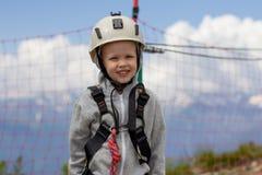 Ο έφηβος στα βουνά μια θερινή ημέρα έντυσε σε ένα σύστημα αναρρίχησης της ασφάλειας στοκ εικόνα με δικαίωμα ελεύθερης χρήσης