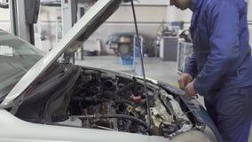 Ο αρσενικός νέος αυτόματος ειδικός σφίγγει τα καρύδια με ένα γαλλικό κλειδί στην κουκούλα του αυτοκινήτου για την επισκευή ή την  απόθεμα βίντεο
