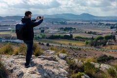 Ο αρσενικός τουρίστας παίρνει τη φωτογραφία με την κινητή τηλεφωνική κάμερα στοκ φωτογραφία