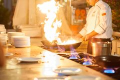 Ο αρχιμάγειρας στην κουζίνα του εστιατορίου στη σόμπα με ένα τηγάνι, μάγειρες πέρα από την υψηλή θερμότητα στοκ εικόνα