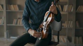 Ο βιολιστής τρίβει το βιολί από τη σκόνη με ένα κουρέλι Μουσικός που φροντίζει για ένα μουσικό όργανο με την αγάπη 4k σε αργή κίν φιλμ μικρού μήκους
