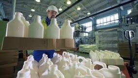 Ο βιομηχανικός εργάτης βάζει τα κιβώτια με τα μπουκάλια σε μια δυνατότητα, που τυλίγει τη διαδικασία απόθεμα βίντεο