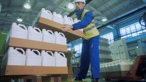 Ο βιομηχανικός εργάτης συσσωρεύει τους δίσκους χαρτοκιβωτίων με τα πλαστικά μεταλλικά κουτιά απόθεμα βίντεο