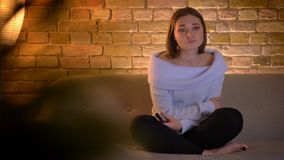 Ο βλαστός κινηματογραφήσεων σε πρώτο πλάνο του νέου όμορφου καυκάσιου θηλυκού που προσέχει μια TV παρουσιάζει και που είναι ευαίσ απόθεμα βίντεο