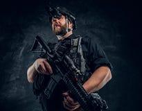 Ο γενειοφόρος στρατιώτης ειδικών δυνάμεων ή ο ιδιωτικός στρατιωτικός ανάδοχος που κρατά ένα επιθετικό τουφέκι και παρατηρεί τα πε στοκ εικόνα