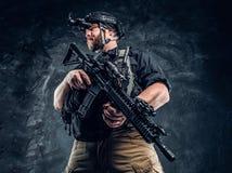 Ο γενειοφόρος στρατιώτης ειδικών δυνάμεων ή ο ιδιωτικός στρατιωτικός ανάδοχος που κρατά ένα επιθετικό τουφέκι και παρατηρεί τα πε στοκ φωτογραφίες με δικαίωμα ελεύθερης χρήσης