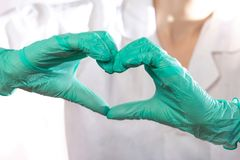 Ο γιατρός στα μπλε ομοιόμορφα και γάντια λατέξ που παρουσιάζουν χειρονομία καρδιών, κλείνει επάνω στοκ εικόνες