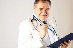 Ο γιατρός της ιατρικής χαμογελά, κρατώντας τα γυαλιά και έναν φάκελλο για τα αρχεία στοκ εικόνα