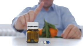 Ο γιατρός που κάνει ένα χέρι προειδοποίησης να υπογράψει για την κατάχρηση φαρμάκων που συμφωνεί με τα φρούτα καταναλώνει στοκ εικόνα