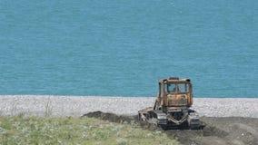 Ο εκσακαφέας ενισχύει την ακτή στα πλαίσια μιας ήρεμης μπλε θάλασσας Ημέρα, ηλιόλουστη, καλοκαίρι απόθεμα βίντεο