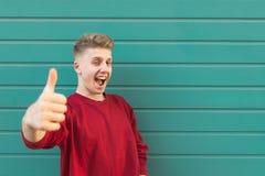 Ο εκφραστικός νεαρός άνδρας στέκεται στο υπόβαθρο ενός τυρκουάζ τοίχου, της παρουσίασης αντίχειρες επάνω και να εξετάσει τη κάμερ στοκ φωτογραφία με δικαίωμα ελεύθερης χρήσης