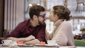 Ο ενήλικοι άνδρας και η γυναίκα φλερτάρουν ο ένας με τον άλλον που κάθεται σε έναν καφέ φιλμ μικρού μήκους