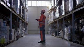 Ο εργαζόμενος αποθηκών εμπορευμάτων με τα γυαλιά στο σκληρό κράνος και ομοιόμορφος κάνει τις σημειώσεις για την ταμπλέτα κατά τη  απόθεμα βίντεο