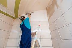 Ο εργαζόμενος βάζει επάνω τον τοίχο από τη σκάλα στο διαμέρισμα είναι κάτω από την κατασκευή, αναδιαμόρφωση, ανακαίνιση, εξέταση στοκ εικόνες με δικαίωμα ελεύθερης χρήσης