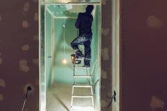 Ο εργαζόμενος βάζει επάνω το ανώτατο όριο από τη σκάλα στο διαμέρισμα είναι κάτω από την κατασκευή, αναδιαμόρφωση, ανακαίνιση, εξ στοκ φωτογραφία με δικαίωμα ελεύθερης χρήσης