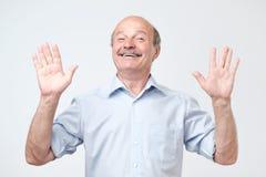 Ο εύθυμος τύπος αυξάνει τα χέρια όπως παρουσιάζει ότι όντας, έχει ευτυχής να κοιτάξει στοκ εικόνες με δικαίωμα ελεύθερης χρήσης