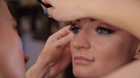 Ο επαγγελματικός καλλιτέχνης makeup κάνει makeup μια πολύ όμορφη γυναίκα απόθεμα βίντεο
