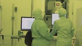 Ο επιστήμονας δύο μηχανικών στις φόρμες μασκών αποστειρωμένες πηγαίνει στην καθαρή περιοχή υψηλή τεχνολογία που κατασκευάζει τη ν απόθεμα βίντεο
