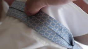 Ο επιχειρηματίας σε έναν μπλε δεσμό ισιώνει το άσπρο πουκάμισο περιλαίμιών του Το πρωί ένας αρσενικός δικηγόρος βάζει σε μια εργα απόθεμα βίντεο