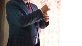 Ο επιχειρηματίας στο κόκκινο κοστούμι ελέγχου δεσμών σκούρο μπλε ισιώνει το μανίκι ενός άσπρου πουκάμισου έννοια μοντέρνος και μο φιλμ μικρού μήκους