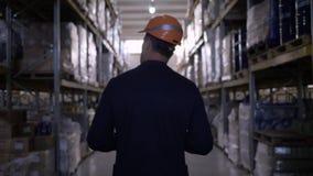 Ο επιχειρηματίας στο σκληρά καπέλο και το κοστούμι που περπατά μέσω της αποθήκης εμπορευμάτων κάνει τις σημειώσεις για την ταμπλέ απόθεμα βίντεο